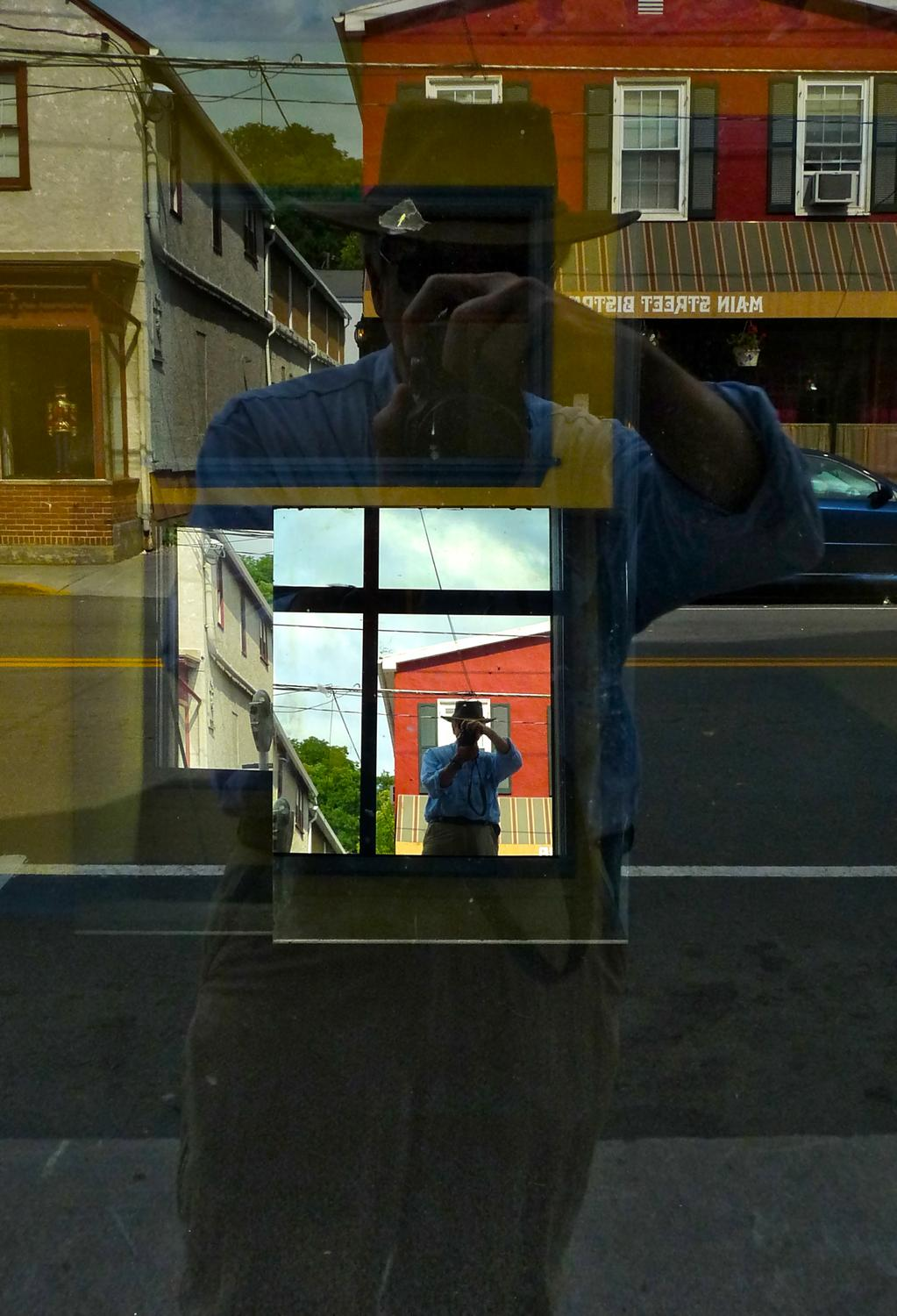 a reflection of the artist in a mirror in a store window - The spirit of René Magritte visits Berryville - Berryville Virginia - Panasonic DMC-FZ28 - Tony Karp, design, art, photography, techno-impressionist, techno-impressionism, aerial photography , drone , drones , dji , mavic pro , video , 3D printing - Books -